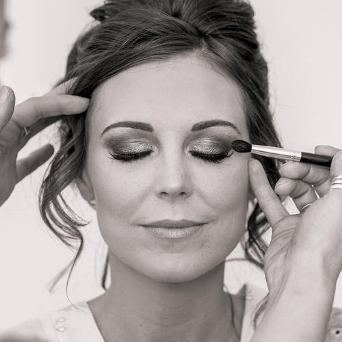Black and white image of a bride having her makeup applied by Rhiannon Pritchard.